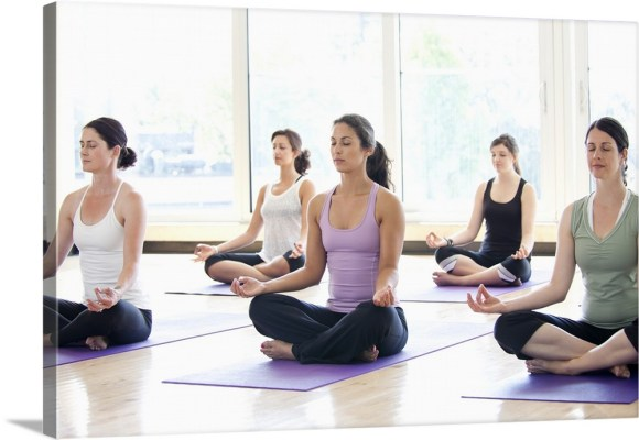 Class of women performing the meditative Sukhasana pose in a ...