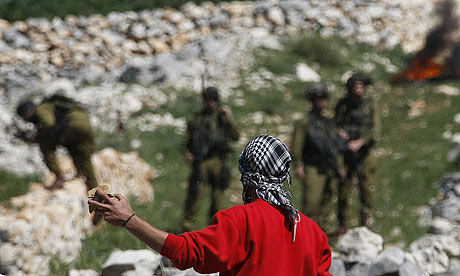 A Palestinian youth throws stones at Israeli troops during clashes in the West Bank