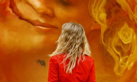 A woman is reflected in one of Anish Kapoor's stainless-steel sculptures