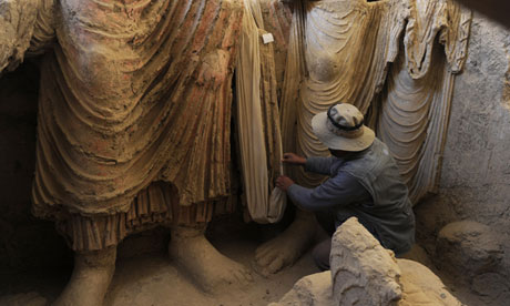 An archaeologist examines the remains of statues of Buddha at Mes Aynak. Photograph: Shah Marai/AFP/Getty Images