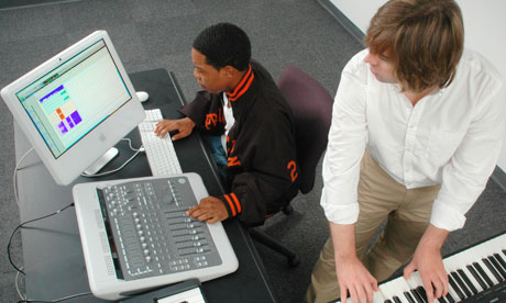 Two men in an audio production session one at keyboard the other at the mixing board