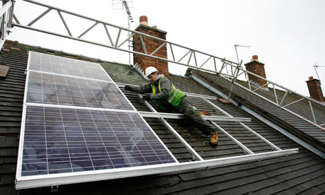 A worker fits solar panels to a roof of a council house in Wrexham , Wales