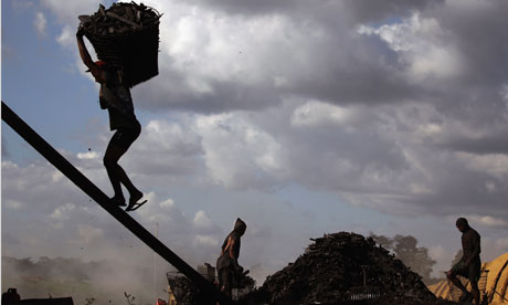 decline of the global environment and population : A worker hauls a bag of charcoal , Brazil