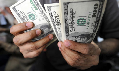 MDG : Remittance and money transfer : A dealer counts US dollar notes