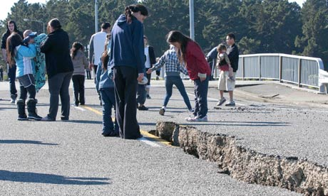 People inspect the earthquake-damaged roadway on the South Brighton Bridge approach