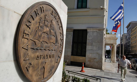 A man makes his way next to a replica of a one drachma coin outside the Athens Town Hall