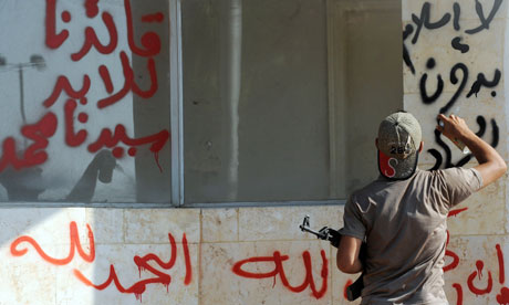 a man sprays an Arabic slogan - No Islam without Jihad - on a wall