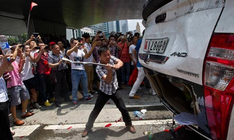 Chinese protester attacks a Honda-brand police car