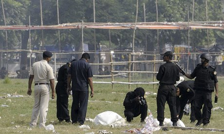 Indian security officials examine debris