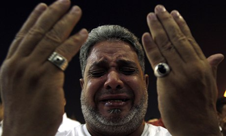 An Egyptian Muslim cries as he performs evening prayers called at Amr Ibn El-Aas mosque, Cairo.