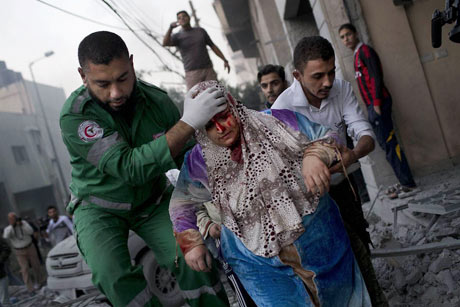 A Palestinian woman is helped after being injured during an Israeli forces strike
