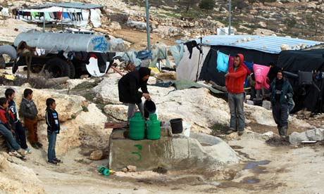 Palestinians fill water canisters from a well in the southern West Bank village of Yatta
