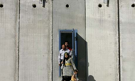 Palestinians walk through a door in a section of the barrier between Jerusalem and the West Bank