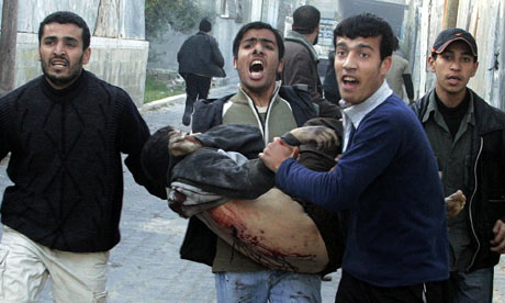 A wounded Palestinian is carried near a UN school in Jabalya, Gaza Strip