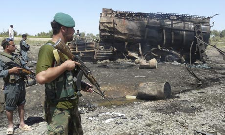 Afghan security forces guard a burned out tanker in Kunduz, after a Nato air strike killed civilians