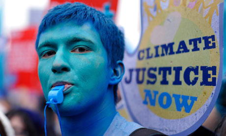 A climate change demonstrator with his face painted blue protests in London.