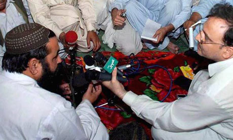 Taliban leader Baitullah Mehsud, left, talks to reporters in South Waziristan in May 2008