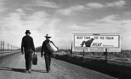 Two men walking along a dusty depression-era road, USA