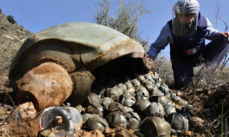 An expert from the Mines Advisory Group inspects an Israeli cluster bomb in Ouazaiyeh, Lebanon