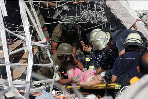 Chile Earthquake: Rescue workers help an injured woman in Concepcion, Chile