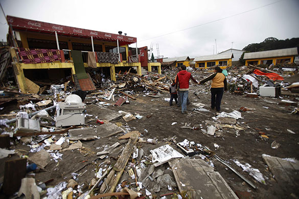 Chile earthquake: People walk in a damaged area of Curanipe, southwest of Santiago