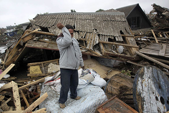 Tsunami damage: A man stands on a mattress where his home used to be in Constitucion, Chile