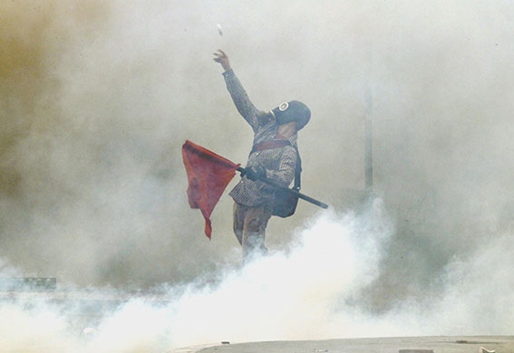 Strike in Greece: A demonstartor hurls projectiles at riot police