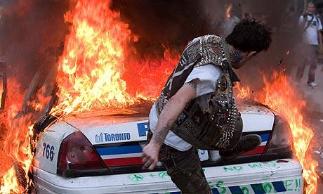 https://i1.wp.com/static.guim.co.uk/sys-images/Guardian/Pix/pictures/2010/6/27/1277636676294/A-protester-kicks-a-burni-006.jpg