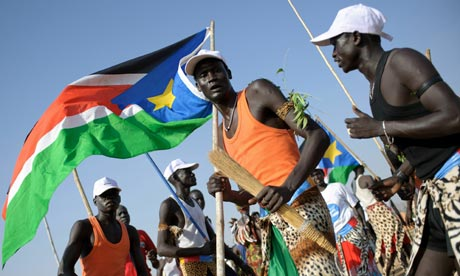 A group of southern Sudanese men wave local flags and dance outside a polling station in Juba