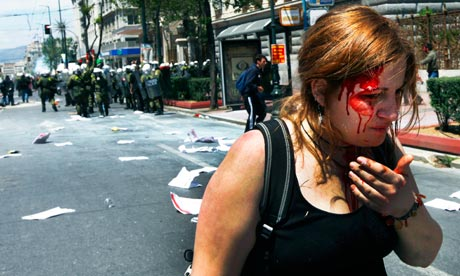 An injured protester bleeds following clashes with riot police in central Athens