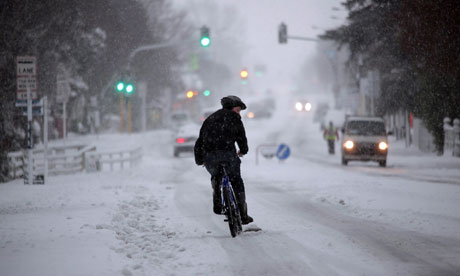 A cyclist is seen riding after heavy snowfalls have blanketed large parts of New Zealand