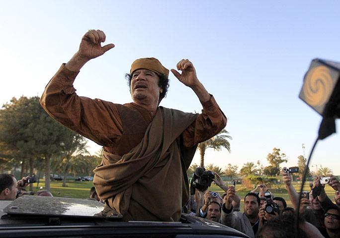 Gaddafi: 10 April 2011: Libyan leader Muammar Gaddafi cheers his supporters
