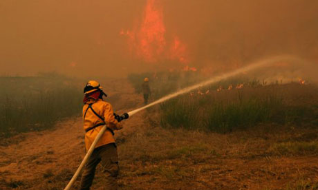 Firefighters in Smithville, Texas: Governor Rick Perry, has called climate change an 'unproven theory' while wildfires ravage his drought-scorched state.