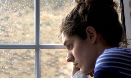Sad/depressed young woman by rainy window