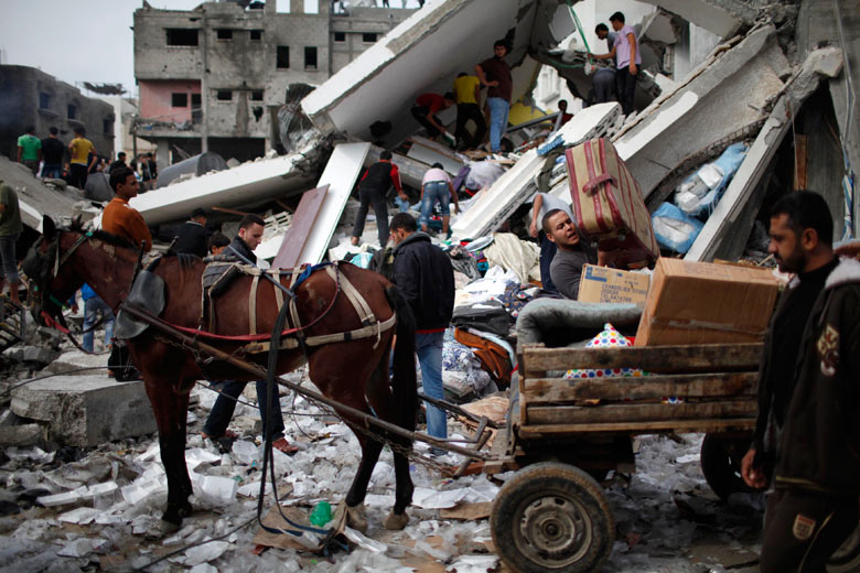 Palestinians load their belongings onto a horse cart after an Israeli air strike