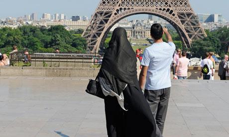 A woman wearing niqab walks at Square Trocadero near the Eiffel Tower in Paris