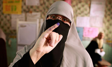 A woman shows her ink-stained finger after casting her vote at a polling station in Cairo