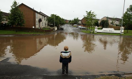 A child stands at the edge of a flooded road in Lisburn, Northern Ireland