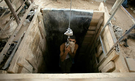 A Palestinian tunnel worker is lowered into one of the tunnels on the Egyptian border in Rafah, Gaza
