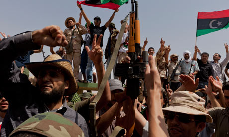 Libyan rebels celebrate at a checkpoint after a deal is made with the elders of Bani Walid