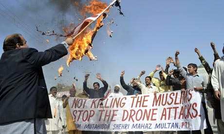 A Pakistani protester holds a burning US