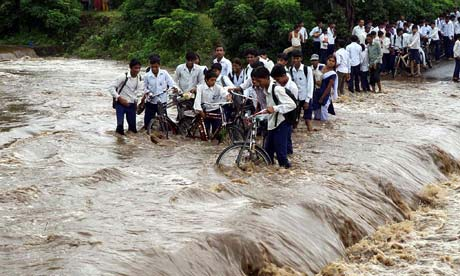 School children encounter flood water after heavy rains in Jhabua, central India
