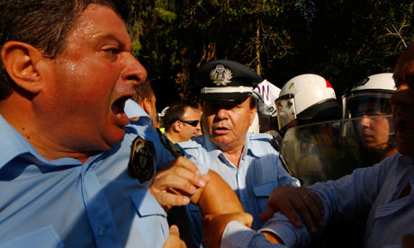 Greek policemen clash with riot police during a protest about austerity cuts in Athens