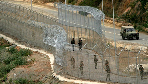 Spanish soldiers patrol along the barrier which separates Spain's North African enclave of Melilla from Morocco