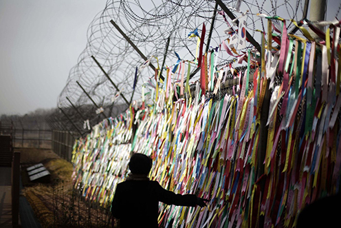 A tourist in South Korea touches ribbons tied to the fence marking the border with North Korea