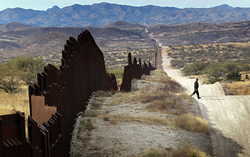 A US border patrol agent looks for footprints from illegal immigrants crossing the US-Mexico border