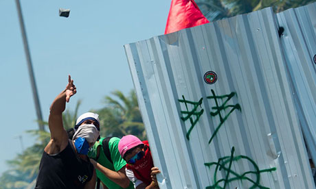 Protesters throw rocks from behind a shield outside the Libre oilfield auction in Rio de Janeiro