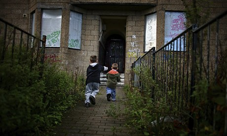 Two young boys play in front of boarded-up houses in Govan, Glasgow