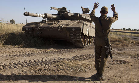 An Israeli soldier directs a Merkava tank in the Golan Heights near the Quneitra crossing with Syria