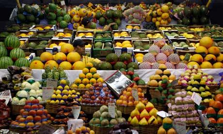 A vendor arranges fruits at a market in São Paulo